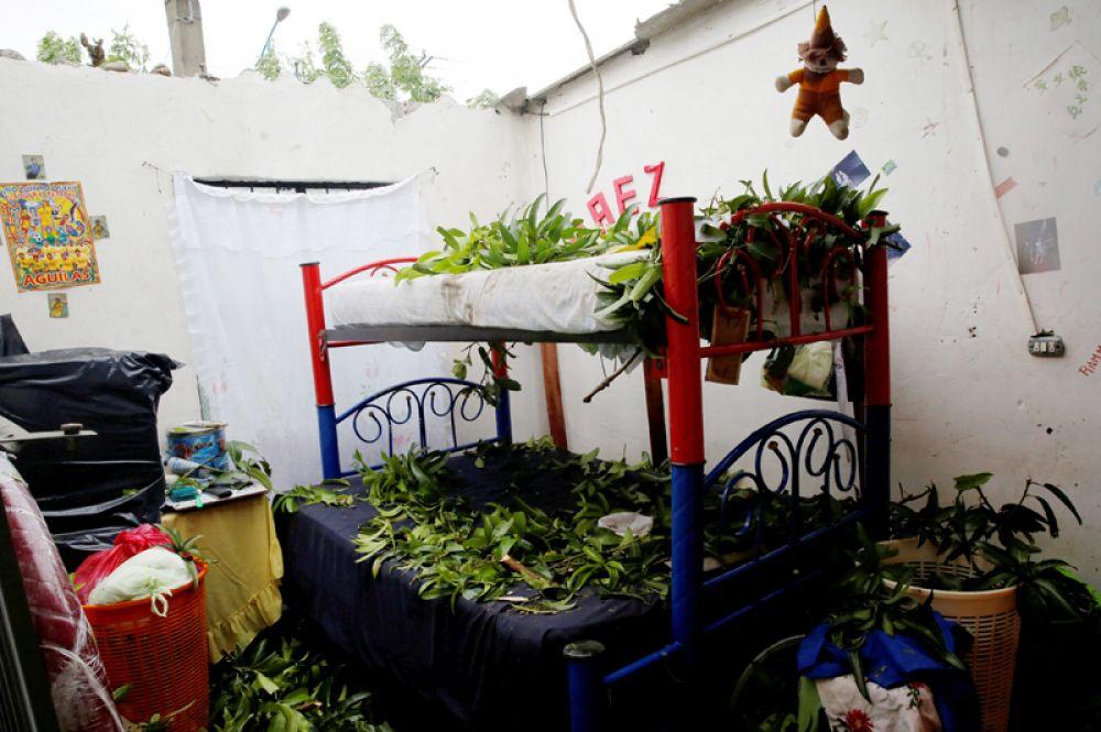 Ветки и обломки деревьев на кроватях в доме, крыша которого была повреждена ураганом.