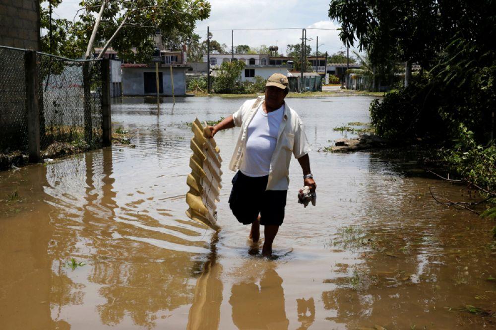 Человек переходит затопленную улицу после урагана ураган «Франклин» в городе Наутла.