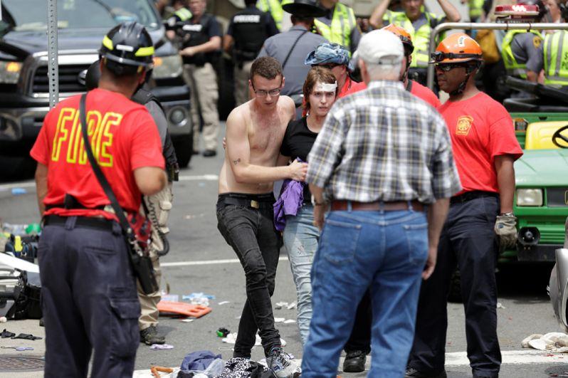Женщине, раненой в результате наезда автомобиля на толпу протестующих, оказывают помощь.