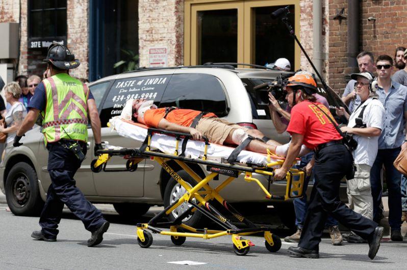 Спасатели перевозят потерпевшего, который был ранен, когда автомобиль наехал на толпу протестующих.