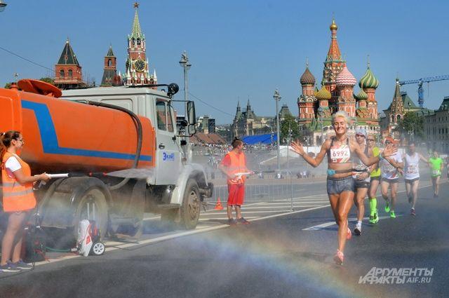 Судьи не только фиксировали соблюдение правил забега, но и охлаждали бегунов в этот жаркий день живительными струями воды.