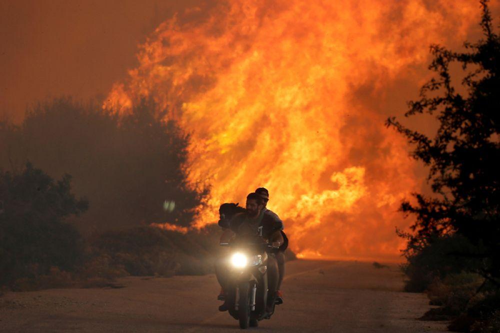 Местные жители на мотоцикле спасаются от лесных пожаров возле деревни Варнавас.