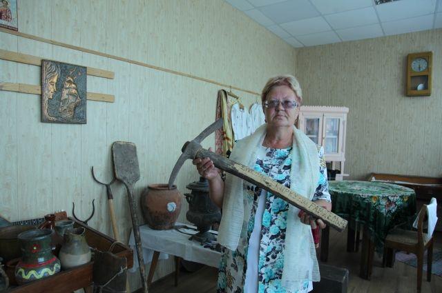 Хранитель музея Любовь Снитко показывает кирку, которой работали когда-то пленные немцы.
