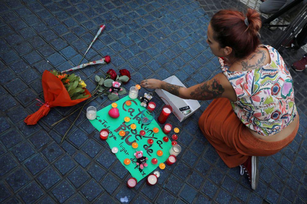 Цветы и свечи на улице Рамбла в Барселоне. Надпись на плакате: «Каталония — место мира».