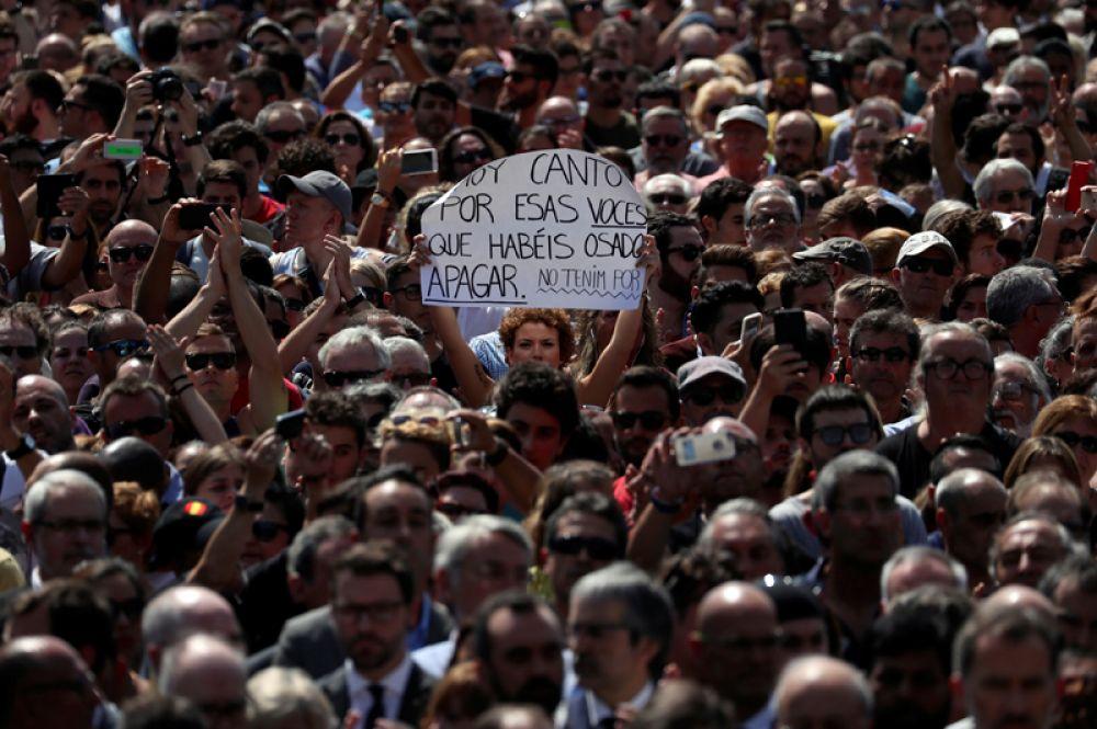 Женщина на площади Пласа-де-Каталунья держит плакат, который гласит: «Я пою сегодня для тех голосов, которые вы осмелились заткнуть. Мы не боимся».