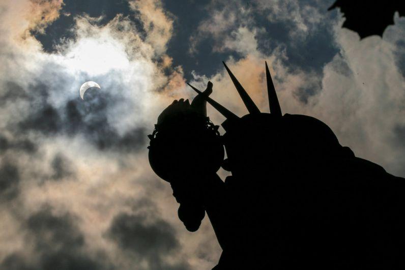 Частичное солнечное затмение над статуей Свободы в Нью-Йорке.