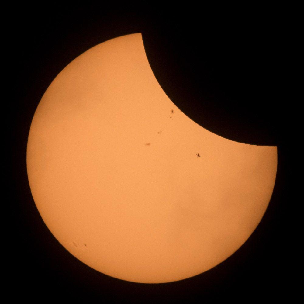 Силуэт МКС на фоне солнечного затмения.