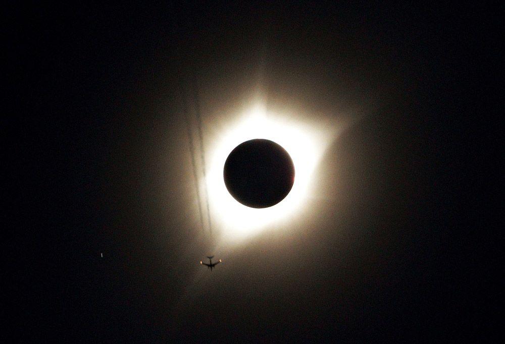 Самолет пролетает на фоне солнечного затмения. Гернси, штат Вайоминг.