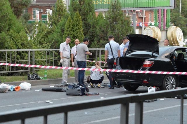 Сотрудники правоохранительных органов проводят следственные действия на месте перестрелки пассажира автомобиля с полицией
