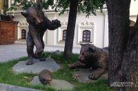 Скульптурная композиция, расположенная под тенистыми деревьями, изображает тигрят, которые выскочили из своего убежища и играют с ежом, которого, судя по всему, увидели впервые в жизни.