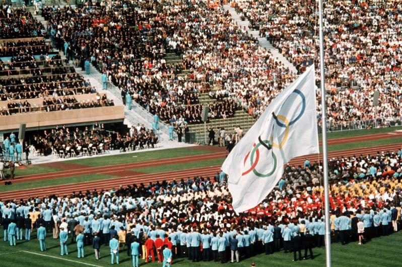 После гибели израильских спортсменов Олимпиада была прервана на сутки. На фото: траурная церемония в память о жертвах теракта на стадионе Мюнхена 6 сентября 1972 года. Делегаты команд занимают позицию на поле, олимпийский флаг приспущен.
