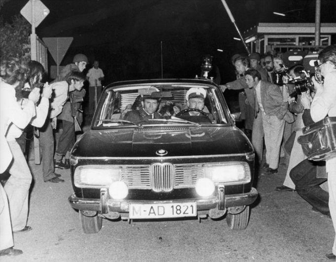 Полицейская машина с арестованным террористом (фигура на заднем сиденье) едет сквозь толпу фотографов в Фюрстенфельдбруке в ночь на 5 сентября 1972 года.