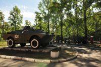 Забор отделяет военную технику от детской площадки.