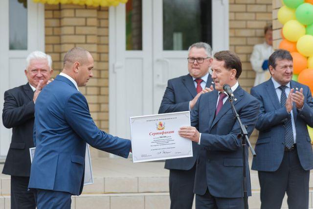 Алексей Гордеев вручил директору школы Роману Ткачёву подарок - сертификаты на получение школьного автобуса и приобретение учебного оборудования.