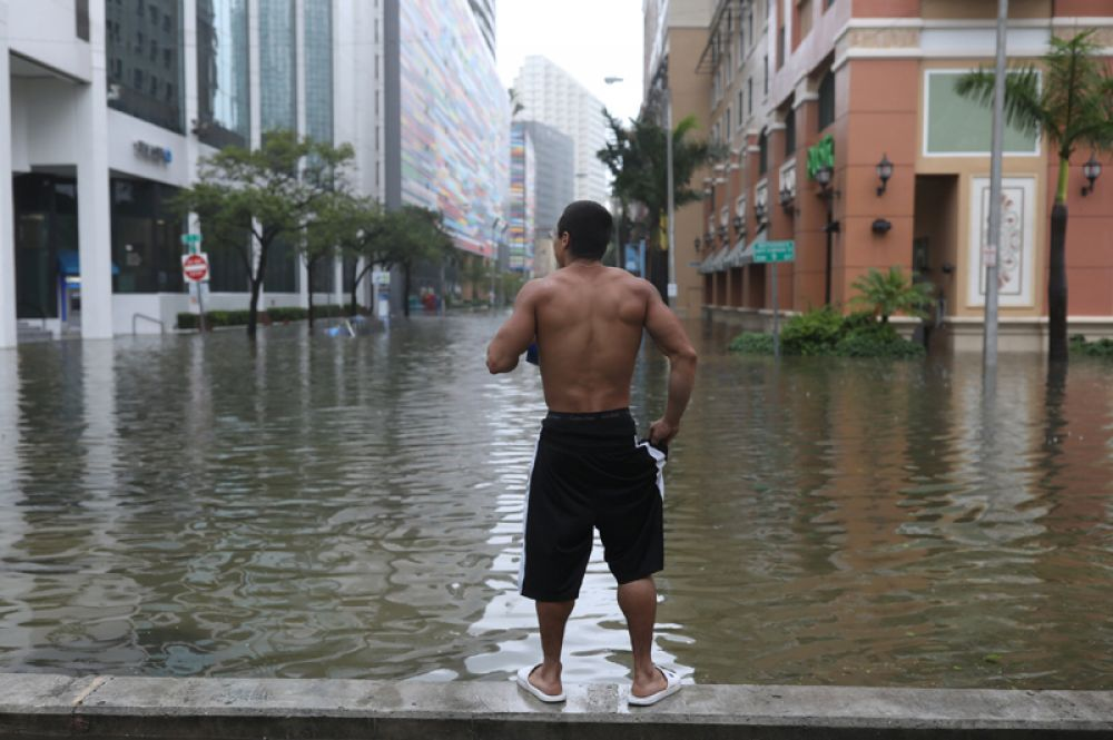 Житель Майами на одной из улиц города, затопленной после урагана.