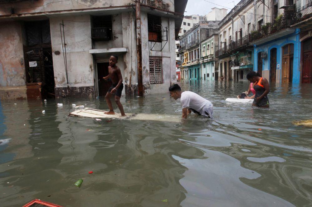 Дети играют на затопленной улице в Гаване.