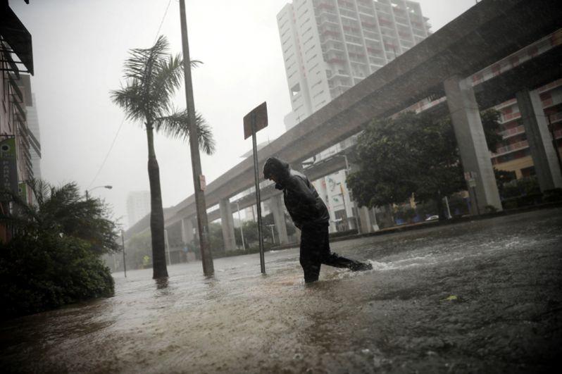 Мужчина переходит затопленную улицу в центре Майами.