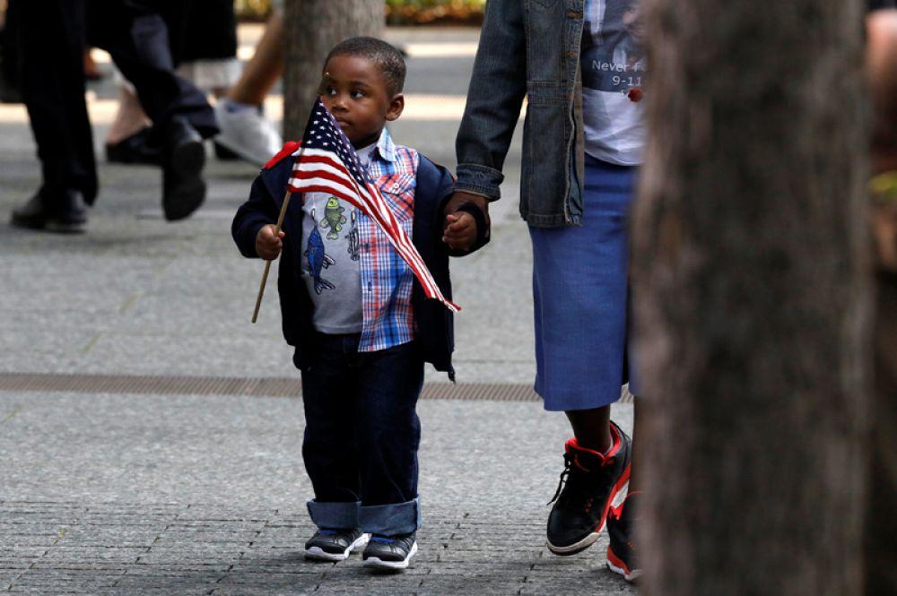 Мальчик с американским флагом во время мероприятий, посвященных 16-й годовщине терактов в Нью-Йорке.