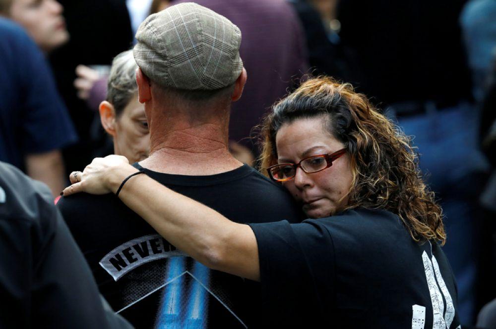 Люди обнимаются в Национальном мемориале и музее 11 сентября во время мероприятий, посвященных 16-й годовщине терактов в Нью-Йорке.