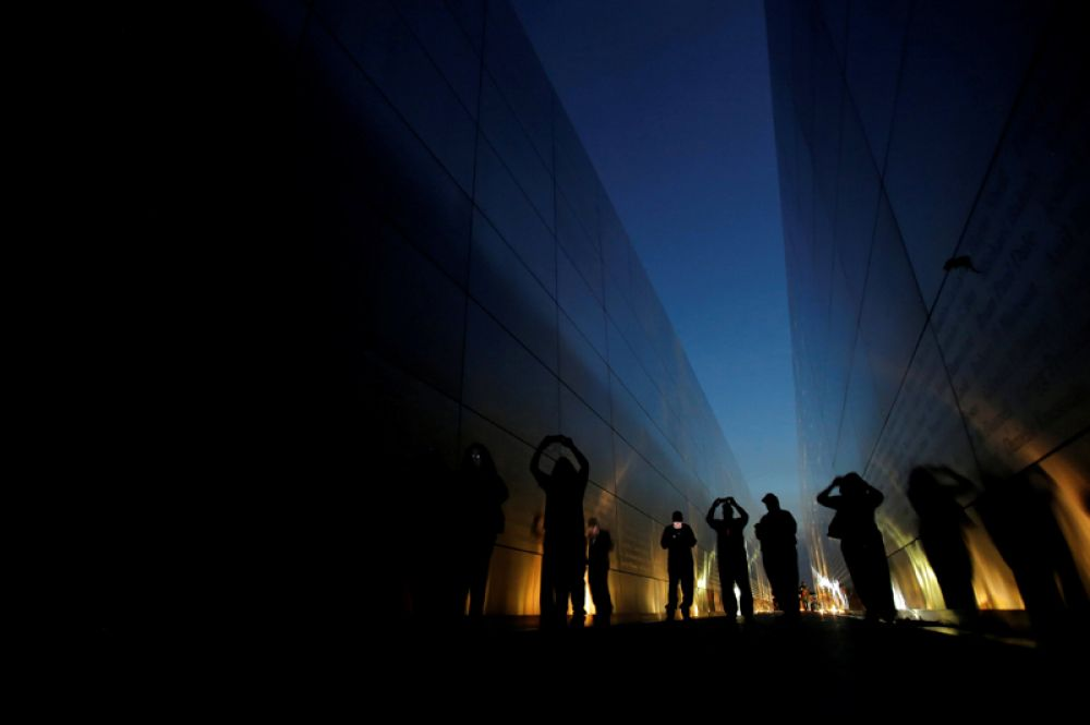 Люди в мемориале «Пустое небо», посвященном 11 сентября. Он представляет собой две стальные стены, символизирующие упавшие башни.