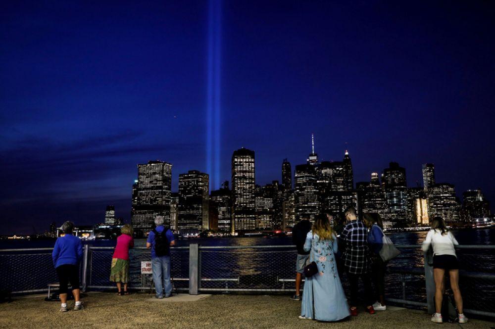 Люди смотрят на памятную инсталляцию «Посвящение в свете» — 88 направленных вверх прожекторов, создающих два мощных луча света.
