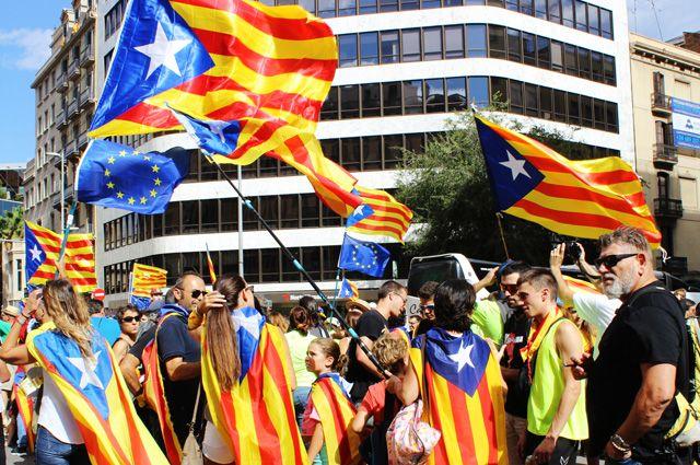 Участники акции в поддержку референдума за независимость и отделение Каталонии от Испании на улицах Барселоны.