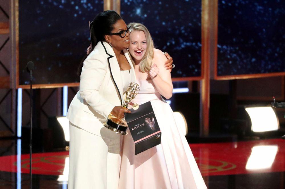 Телеведущая Опра Уинфри поздравляет Элизабет Мосс с победой.