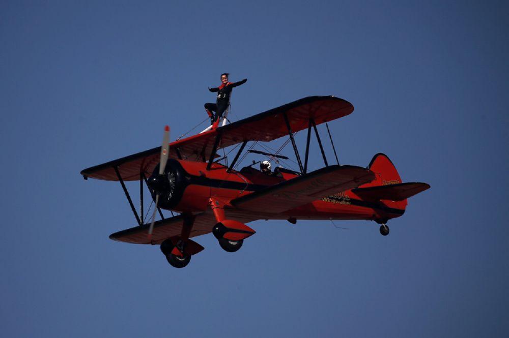 Пилот Даниэль Хьюз выступает на самолёте, пилотируемом Эмилиано Дель Буоно, авиашоу в Танагре.