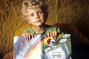 Мальчик с книжкой Н.Носова «Незнайка на луне».