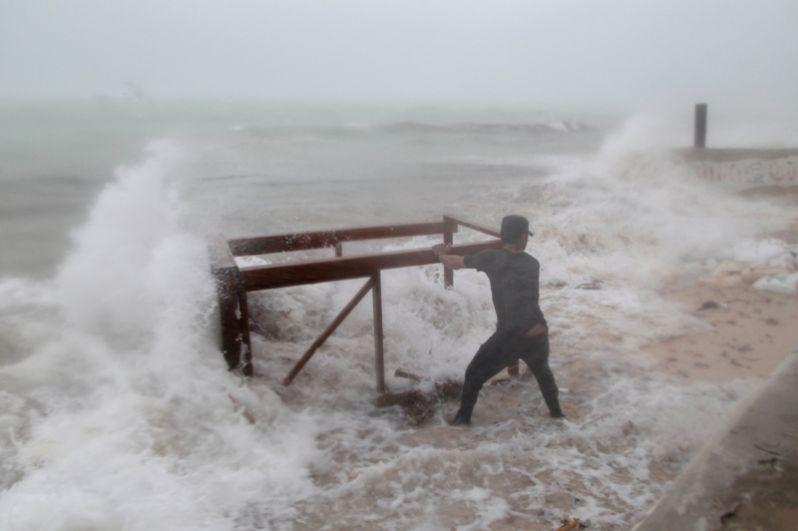 Мужчина пытается спасти стол из своего ресторана во время урагана «Мария» в Пунта-Кана, Доминиканская Респулика.