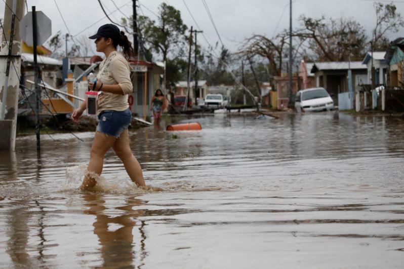 Женщина пробирается через затопленную улицу в Салинасе, Пуэрто-Рико.