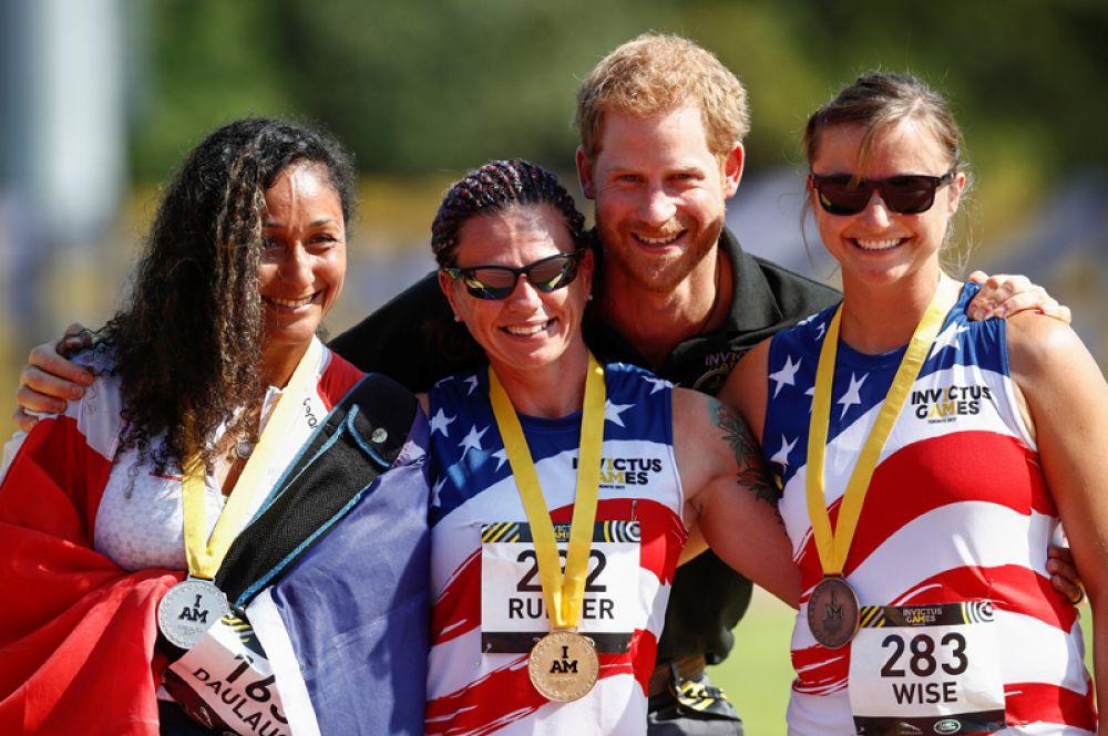 Принц Гарри и призёры в беге на 100 метров среди женщин: Сара Раддер (США, золото), Сабрина Даулаус (Франция, серебро) и Кристи Вайс (США, бронза).