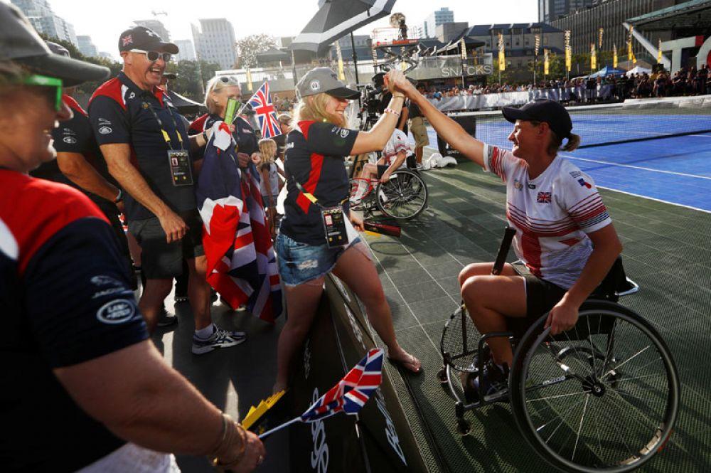 Спортсменка из Великобритании празднует победу в теннисном матче на колясках с Австралией.