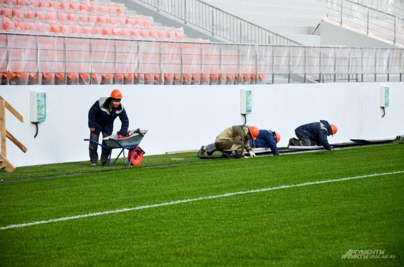 Тем временем рабочие завершают работы по вдоль газона.