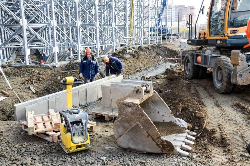 Рабочие роют траншеи под инженерные сети.