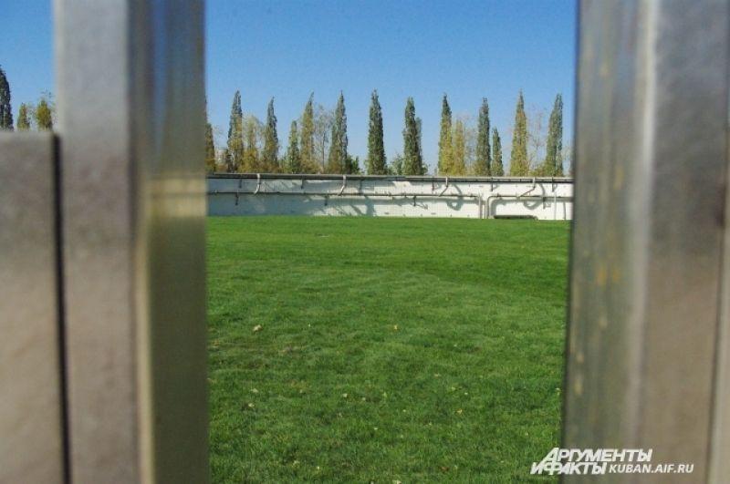 Зеленое поле за забором на территории парка: возможно, оно будет использоваться как футбольное.