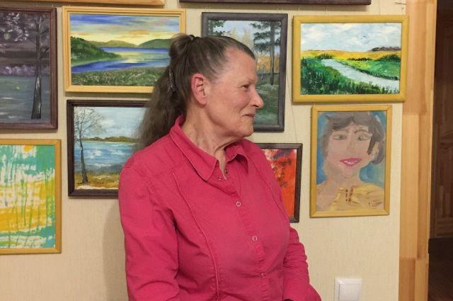 Все стены в квартире Ларисы Михайловны завешаны работами внучки. На фото бабушка рядом с автопортретом Анны.