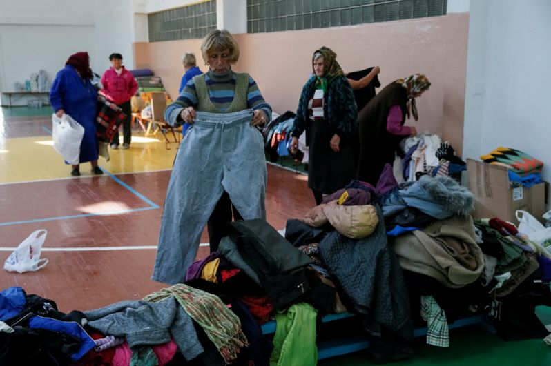 Местные жители, эвакуированные из деревень, расположенных вблизи складов боеприпасов, получают гуманитарную помощь в одной из школ Винницы.