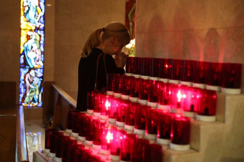 Женщина молится во время мемориальной службы по погибшим на музыкальном фестивале Route 91.