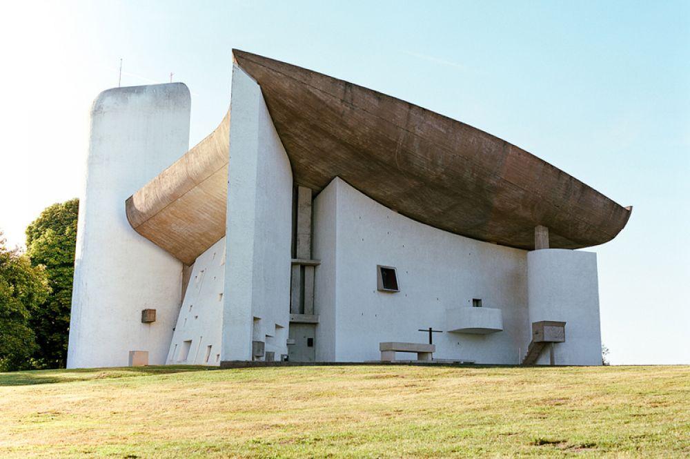Капелла в Роншане или Нотр-Дам-дю-О. Эта бетонная паломническая церковь была построена в 1950-1955 годах во французском местечке Роншан. Часовня церкви идеально вписана в окружающий ландшафт. Криволинейная крыша была навеяна формой раковины, которую Ле Корбюзье подобрал на пляже в Лонг-Айленде. Первоначально нестандартное здание вызывало бурные протесты местных жителей, однако теперь туристы, приезжающие посмотреть на него, стали одним из основных источников дохода роншанцев.