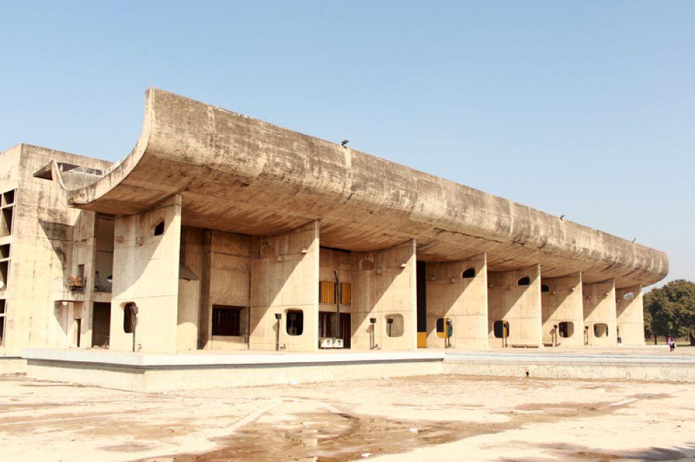 Здание Ассамблеи в городе Чандигарх в Индии. В 1950 году по приглашению индийских властей штата Пенджаб Корбюзье приступил к осуществлению самого масштабного проекта своей жизни — проекта новой столицы штата, города Чандигарх. Город, включающий административный центр и жилые кварталы со всей инфраструктурой, строился в течение десяти лет. Как и в Марсельском блоке, для наружной отделки зданий используется грубый бетон (béton brut). Эта техника, ставшая особенностью нового стиля Ле Корбюзье, была позже подхвачена многими архитекторами Европы других стран.