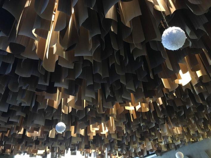 Интерьер выполнен в характерной для американских закусочных манере, а инсталляция из шпона на потолке символизирует рубленое мясо для котлеты, которое проходит через мясорубку.