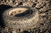 Отлетевшее колесо пронеслось по дороге и упало в грязь