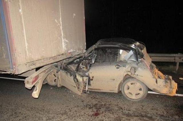 От удара иномарку отбросило под полуприцеп второго грузовика.