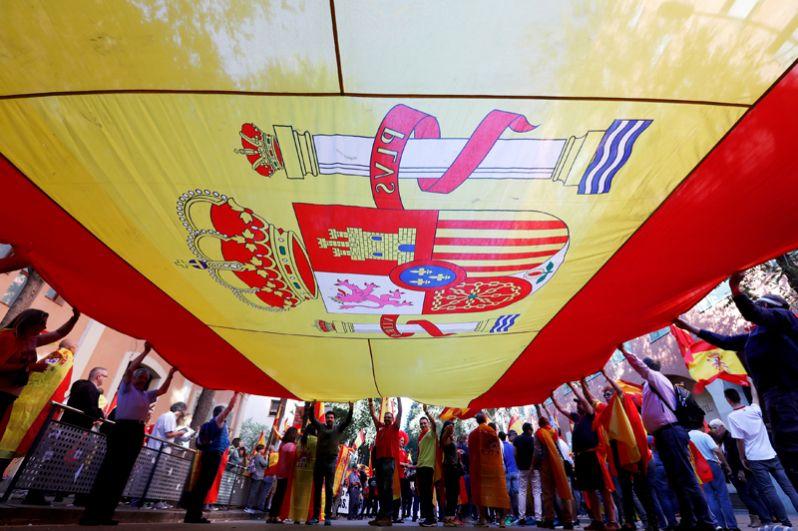 Участники акции держат большой флаг Испании.