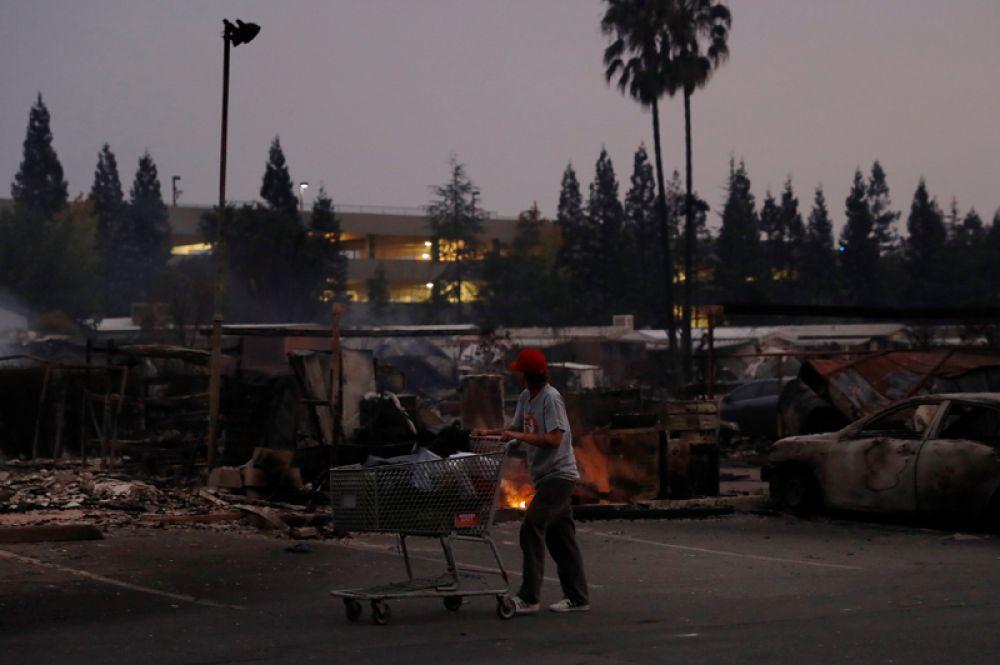 Женщина везет тележку с вещами в городе Санта-Роза.