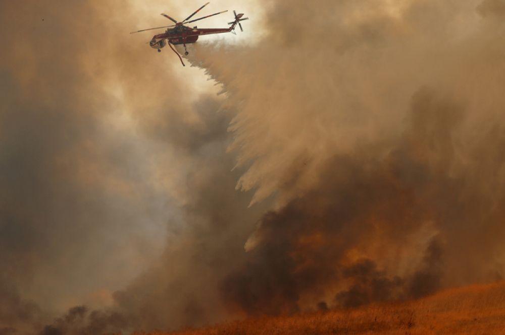 Пожарный вертолет тушит лесной пожар в Ориндже.