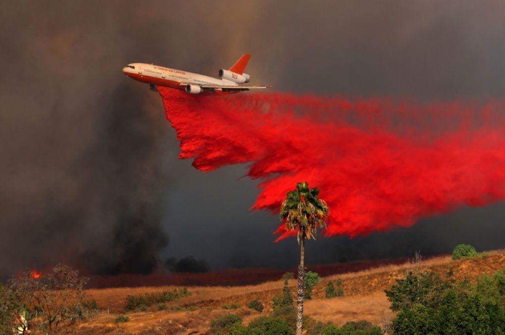 Самолет DC-10 тушит лесной пожар в Ориндже.