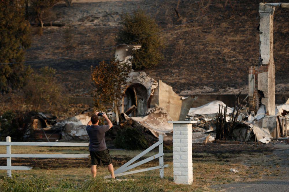 Мужчина фотографирует развалины здания на шоссе 121 в округе Сонома.