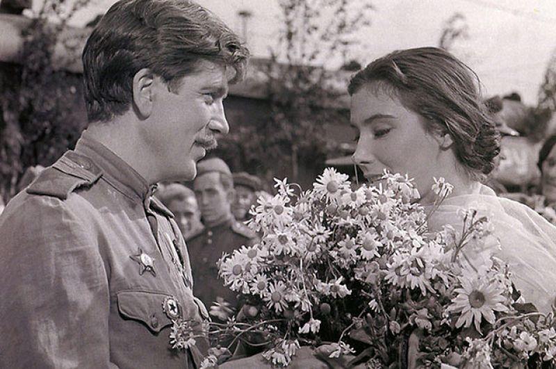 Вероника, не находя Бориса, идёт сквозь толпу и раздаёт цветы из своего букета фронтовикам.